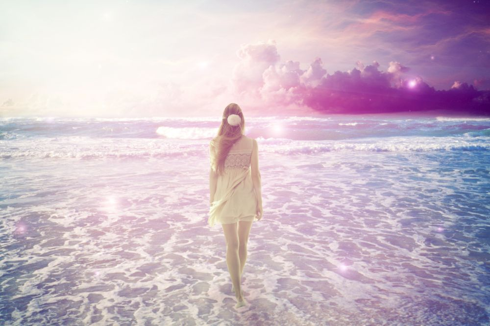 Young woman walking on a dreamy beach enjoying ocean colorful violet sky view. Landscape nature screen saver